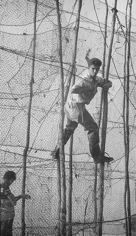 Entre deux rangées de filets de pêche tenus à la verticale par de grandes perches, un homme, s'aidant des perches, se tient en équilibre à environ 3 mètres de haut; photo noir et blanc.