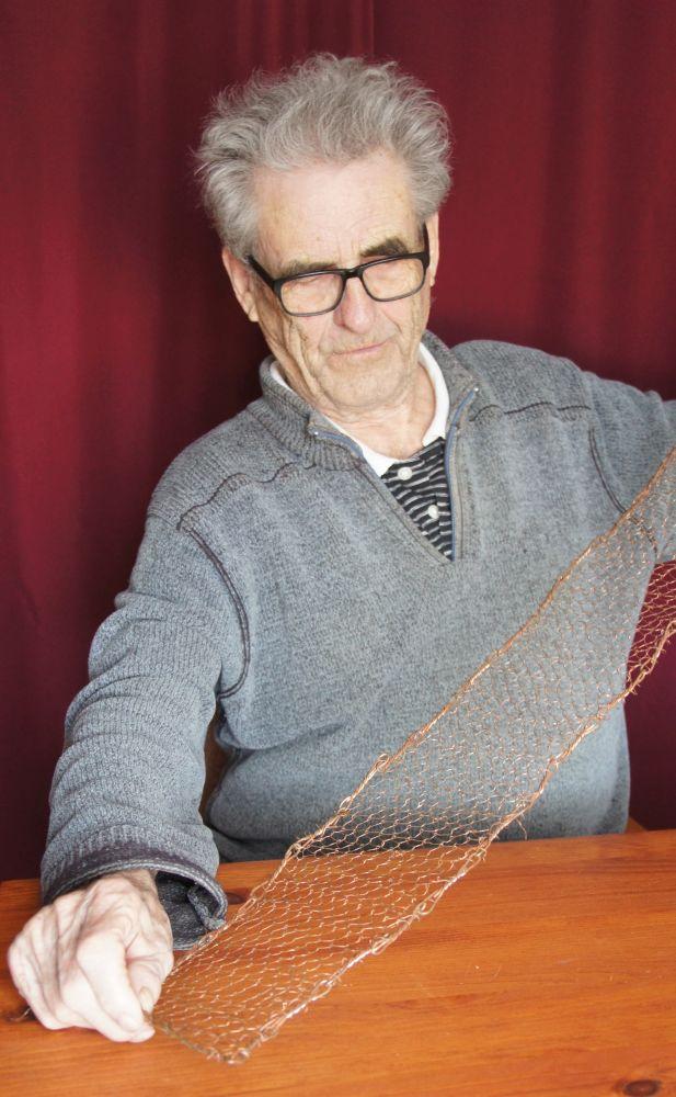 Un octogénaire assis à une table déploie une étroite bande de filet de cuivre entre ses deux mains.