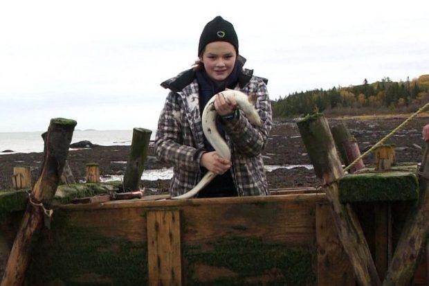 Une adolescente portant une tuque et un manteau est debout dans un coffre en bois servant à garder les anguilles captives dans une pêche. Elle tient une anguille dans ses mains; en arrière-plan, on voit le fleuve et une baie.