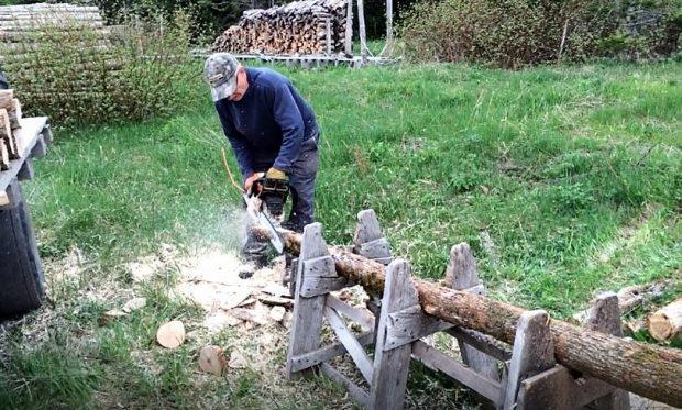 Un homme utilise une scie à chaîne pour tailler en pointe l'extrémité d'un poteau couché sur un tréteau artisanal.