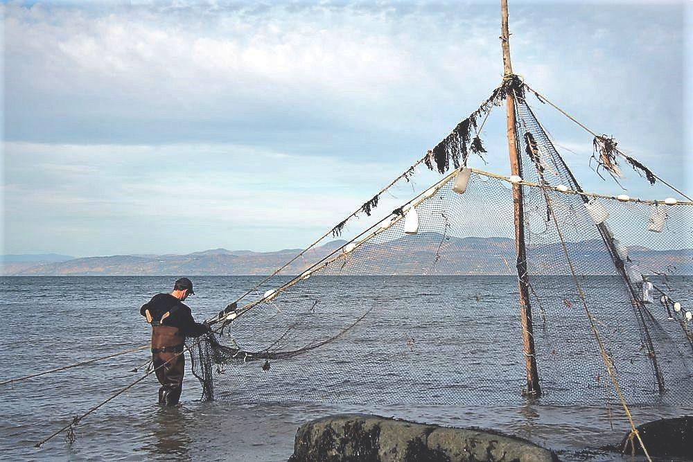 Un homme portant des bottes-pantalon est debout dans l'eau du fleuve et tient la base d'un filet de pêche attaché au sommet d'un poteau de 6 m de haut.