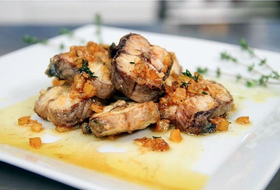 Une assiette carrée dans laquelle se trouvent des tronçons d'anguille grillés et nappés de sauce à l'écorce d'orange.