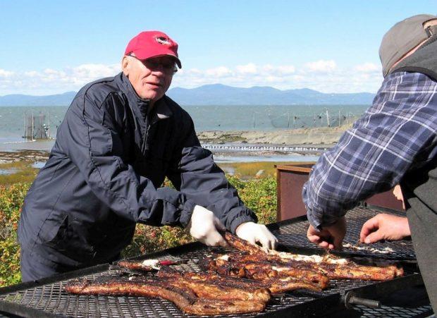 Des anguilles rôtissent sur les grilles d'un B.B.Q. artisanal près du fleuve. Deux hommes s'occupent de la cuisson.