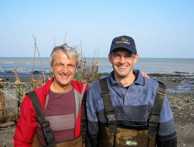 Deux hommes au retour de la pêche à anguilles vus du torse jusqu'à la tête et se tenant amicalement par l'épaule. En arrière-plan, on voit une pêche à anguilles et le fleuve.