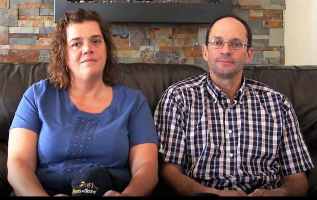 Un couple assis côte à côte sur un divan de cuir brun.