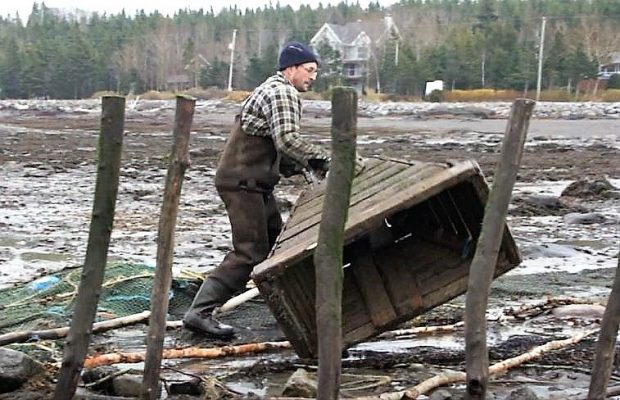 Un homme déplace un gros entonnoir en bois sur la rive du fleuve en le faisant rouler sur lui-même.