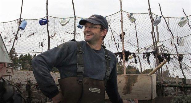Un pêcheur devant les filets de sa pêche à anguilles vu du torse jusqu'à la tête et ayant sa main droite sur sa hanche.