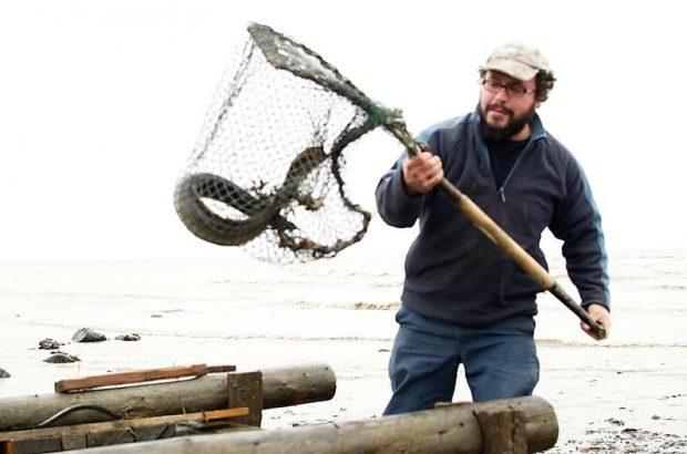 Un pêcheur d'anguilles tient un grand filet attaché à un cadre rigide doté d'un manche et contenant une anguille. On voit le dessus d'un gros coffre en bois au bas de la photo.
