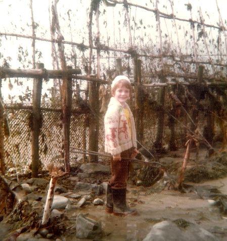Un petit garçon des années 1970 portant des bottes de caoutchouc, une veste et une tuque de laine pose en souriant devant un filet de pêche à anguilles tenu à la verticale. Il a les pieds dans l'eau.