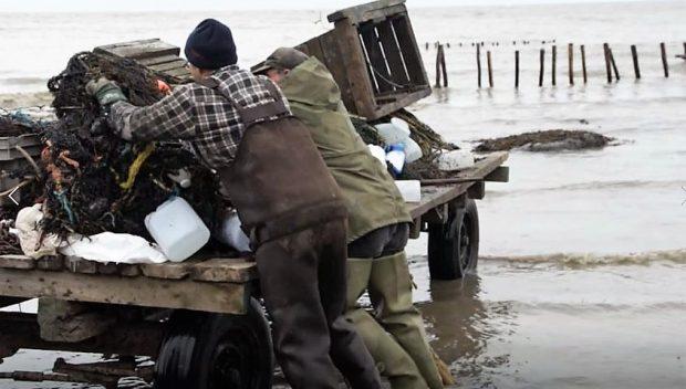 Deux hommes en habit de pêche déposent un filet sur une remorque dont les roues sont dans l'eau montante du fleuve.