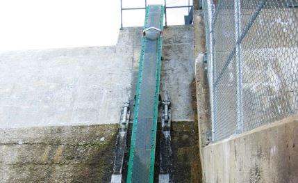 Mur de béton formant un barrage hydro-électrique. Une bande étroite, telle une glissade, est aménagée sur le mur de bas en haut pour que les anguilles puissent y monter.