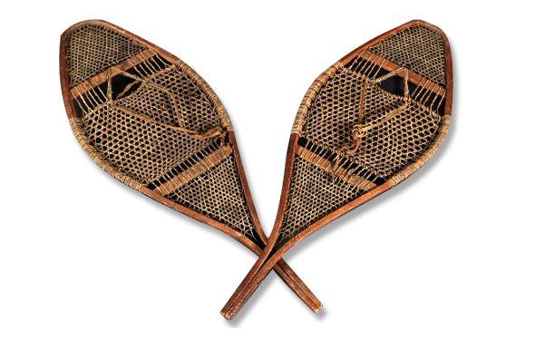 Une paire de raquettes à neige de fabrication artisanale, cadre en bois et tressage en babiche (lanières de cuir).