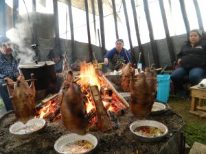A man and two women roast geese over the fire in a teepee
