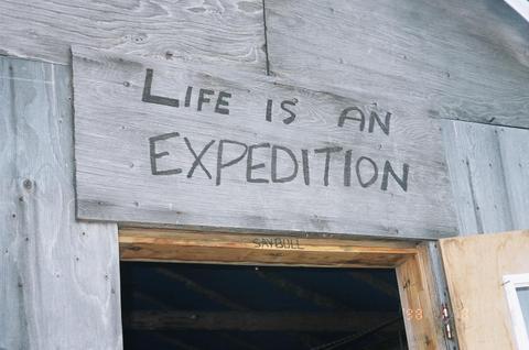 Écriture sur une pièce de bois au-dessus de la porte d'un cabanon non peint.