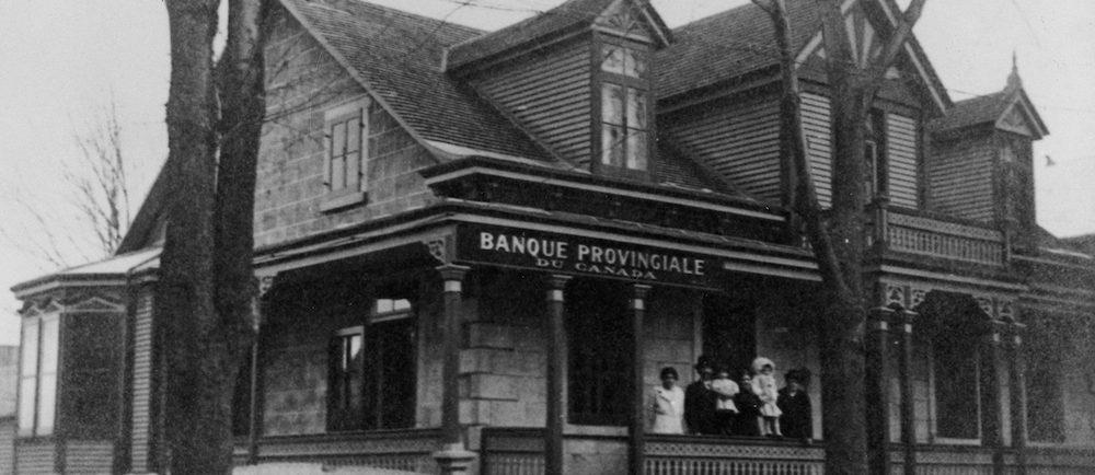 Photographie en noir et blanc d'une maison ancestrale. Il s'agit d'une succursale de la banque provinciale du Canada. Une famille est sur le perron.