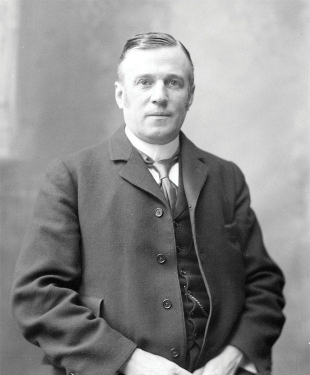 Portrait noir et blanc plan moyen d'un homme (Sir Joseph Pope) posant les mains jointes devant lui, vêtu d'un costume trois pièces avec une cravate sur sa chemise à col haut; on distingue la chaîne d'une montre gousset sur son gilet. Son regard fait face à la caméra.
