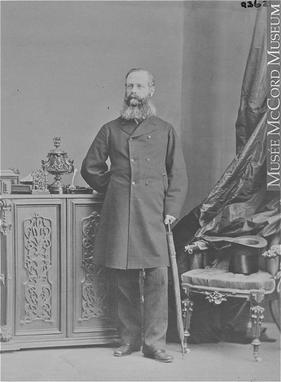 Photographie noir et blanc d'un homme (Lord Monck) debout, s'appuyant sur un parapluie replié, sa main droite derrière son dos, posant à côté d'une chaise sur laquelle il a déposé son haut-de-forme. Il affiche une barbe fournie et porte un pardessus de laine à double boutonnage.