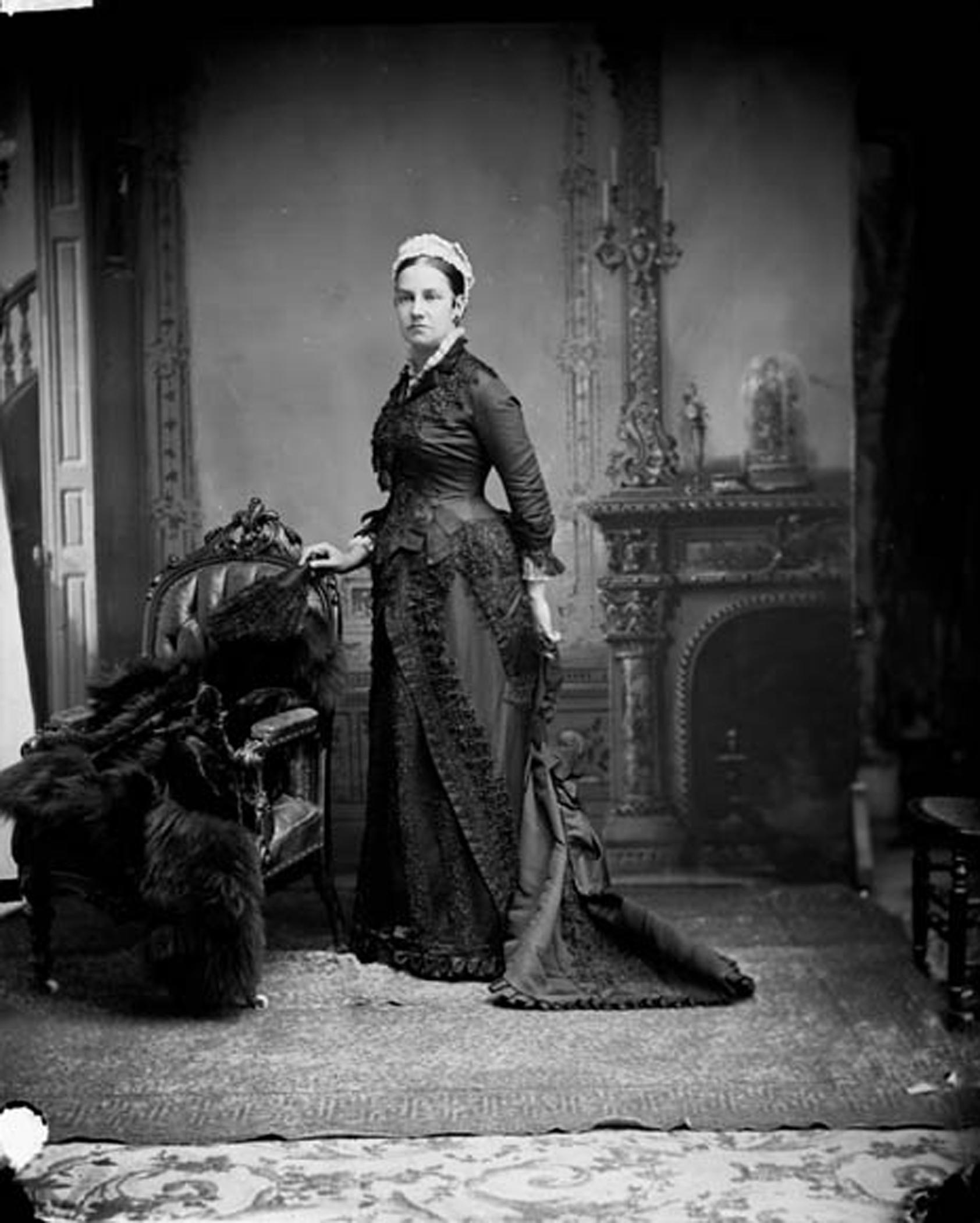 Photo noir et blanc d'une femme (Lady Agnes Macdonald) vêtue d'une longue robe noire, se tenant debout devant un foyer, à côté d'une chaise sur laquelle est déposé un manteau de fourrure.
