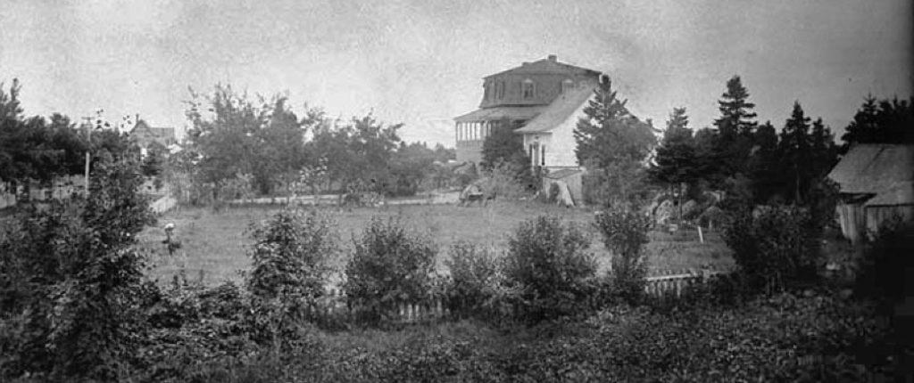 Photo noir et blanc de la villa Les Rochers v. 1883 et de son terrain bordé de conifères. Au premier plan à droite, on aperçoit un hangar en bois et en arrière-plan, la toiture en pointe d'un cottage voisin.