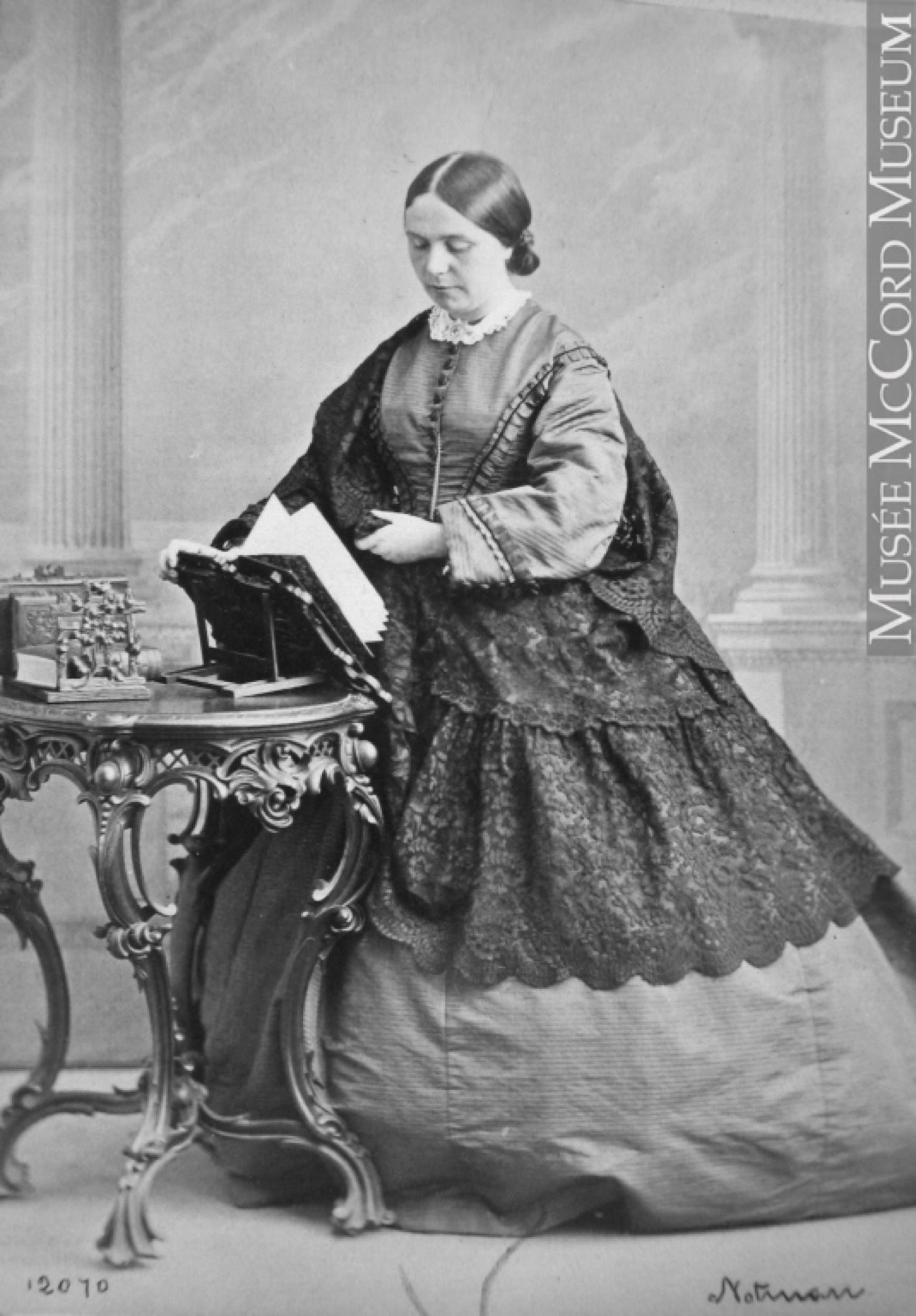Photo noir et blanc d'une femme (Lady Frances Monck) se tenant debout, vêtue d'une large jupe longue drapée de dentelle, tournant les pages d'un livre déposé sur un lutrin devant elle.