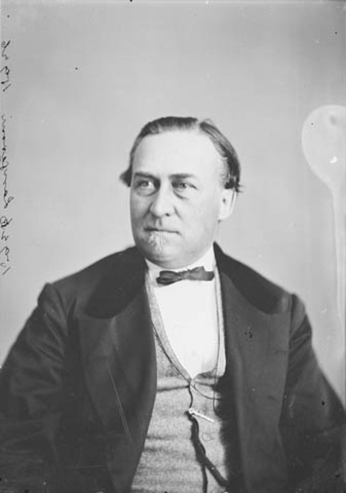 Portrait noir et blanc d'un homme d'âge moyen (Sir Hector Langevin), rasé de près mais affichant une petite barbe au menton, à la chevelure noire, vêtu d'une veste et d'un gilet, affichant un nœud papillon; son regard est songeur, légèrement tourné vers la gauche du cadre.