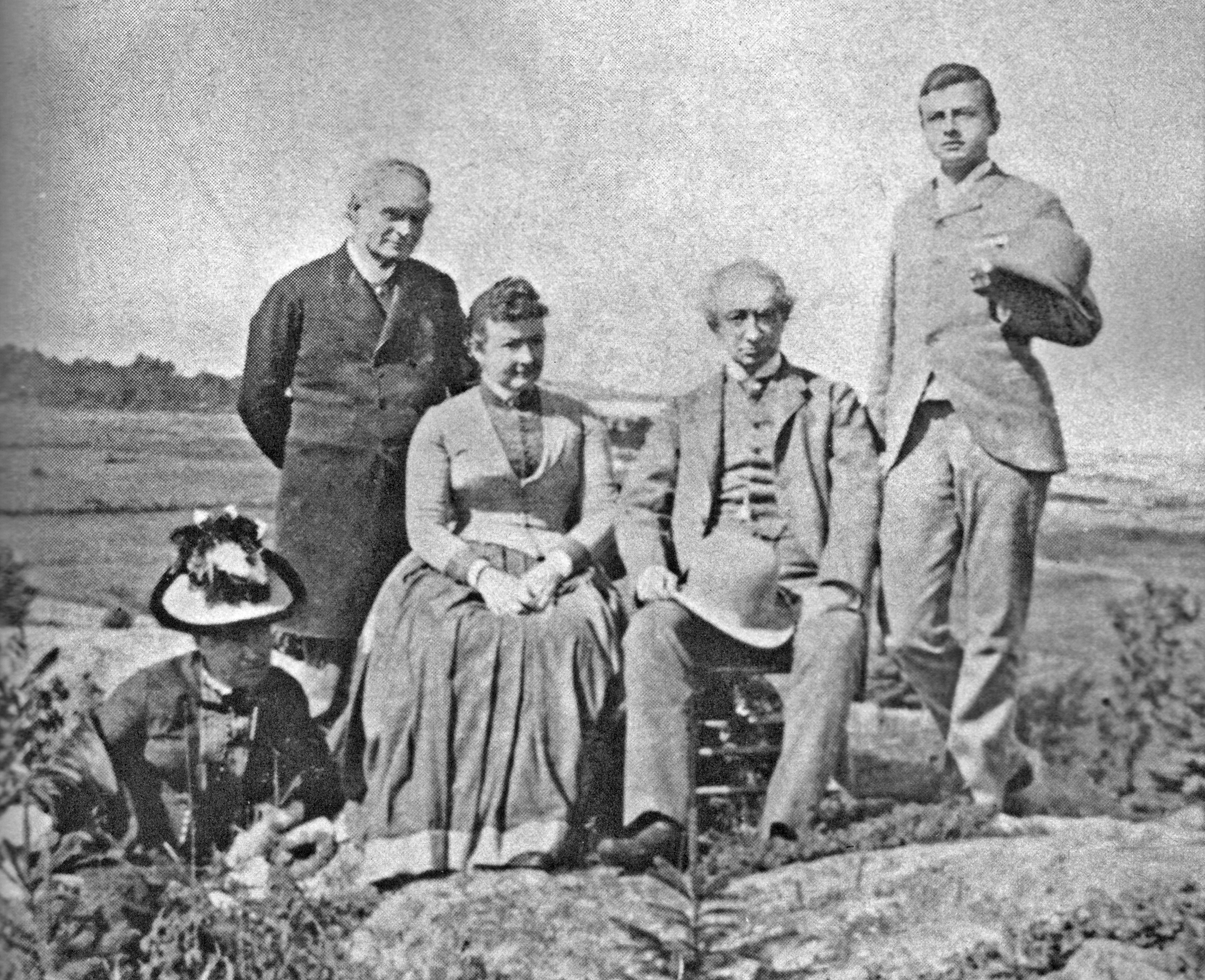 Photo granuleuse noir et blanc montrant cinq adultes (le couple Macdonald et les Tilleys) en positions debout et assise sur un sol rocheux, posant devant le fleuve St-Laurent en arrière-plan.