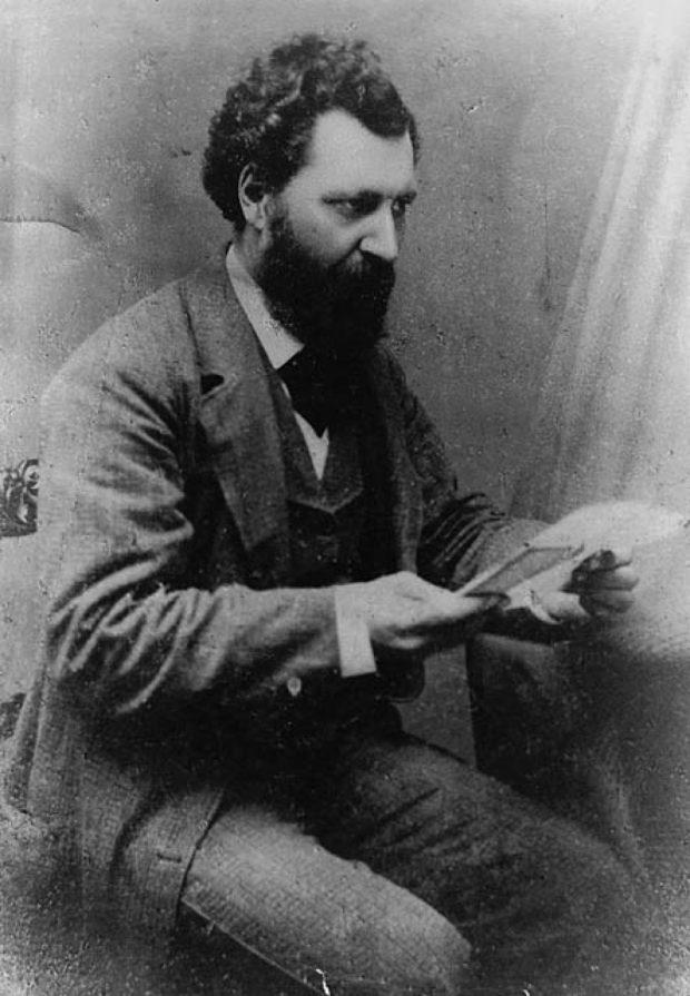 Photographie noir et blanc d'un homme assis (Louis Riel) tenant un document dans sa main, son regard porté vers l'avant. L'homme est barbu, a une chevelure noire bouclée et est vêtu d'un costume en laine avec cravate.