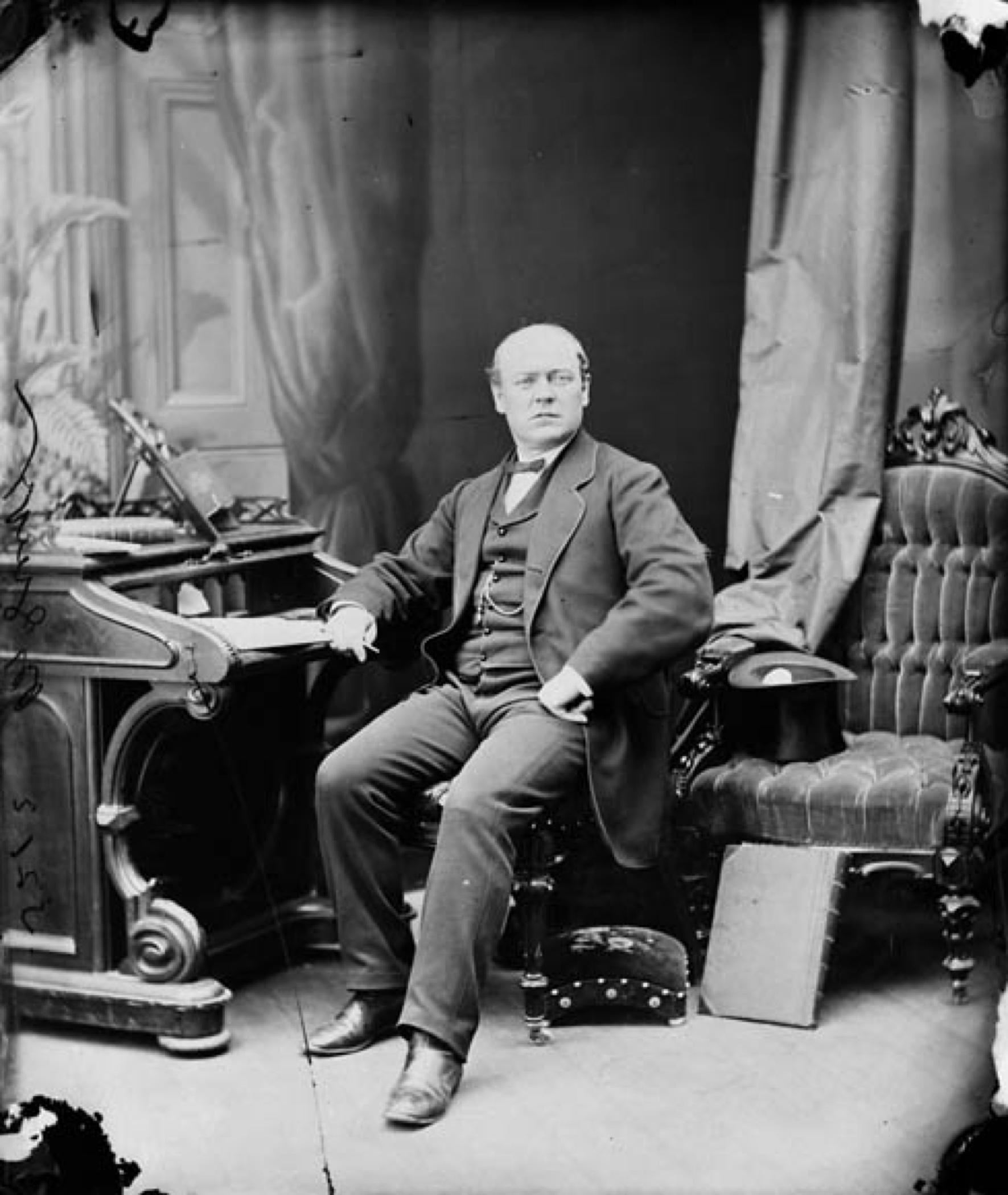 Photo noir et blanc d'un homme d'âge moyen (Sir Thomas McGreevy), partiellement chauve, assis sur une chaise capitonnée, son bras droit appuyé sur un secrétaire; son regard tourné vers la caméra. Il est vêtu d'un costume officiel sombre de style mi-victorien; un chapeau haut-de-forme repose à l'envers sur une autre chaise en velours capitonnée à ses côtés. En arrière-plan, des tentures suspendues dont une devant une porte.