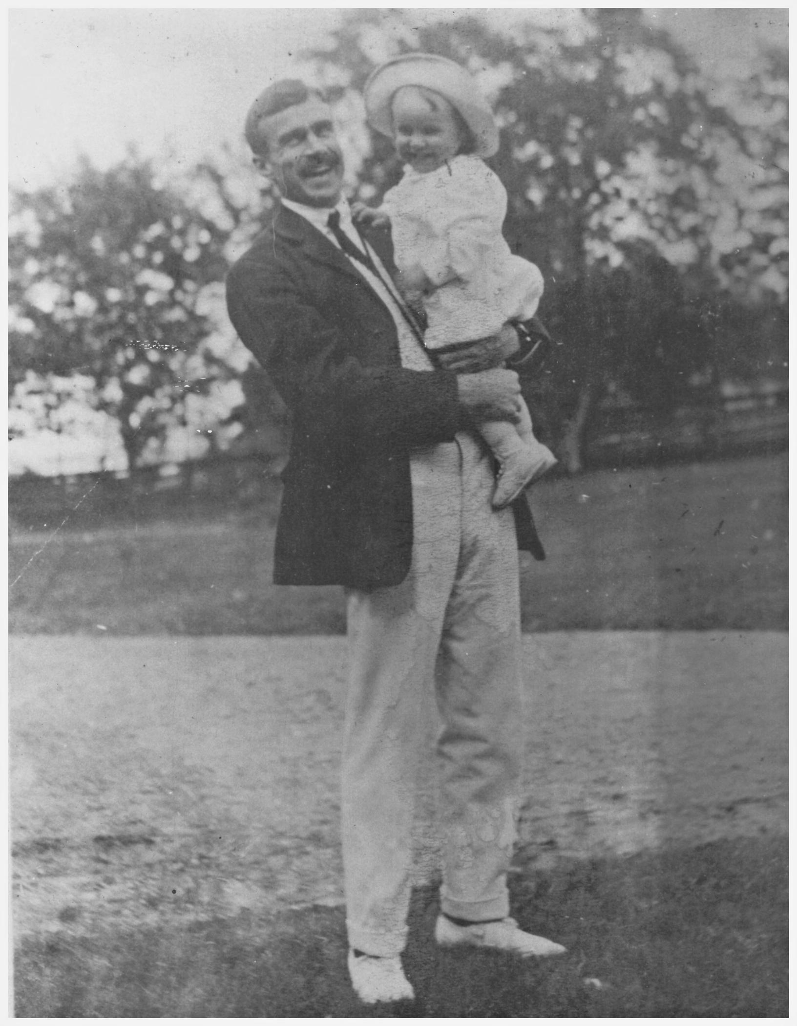 Photographie noir et blanc d'un homme de grande taille (Kenneth Molson), souriant, tenant dans ses bras un enfant en bas âge, lui aussi souriant, posant à l'extérieur sur une pelouse devant une rangée d'arbres en arrière-plan.