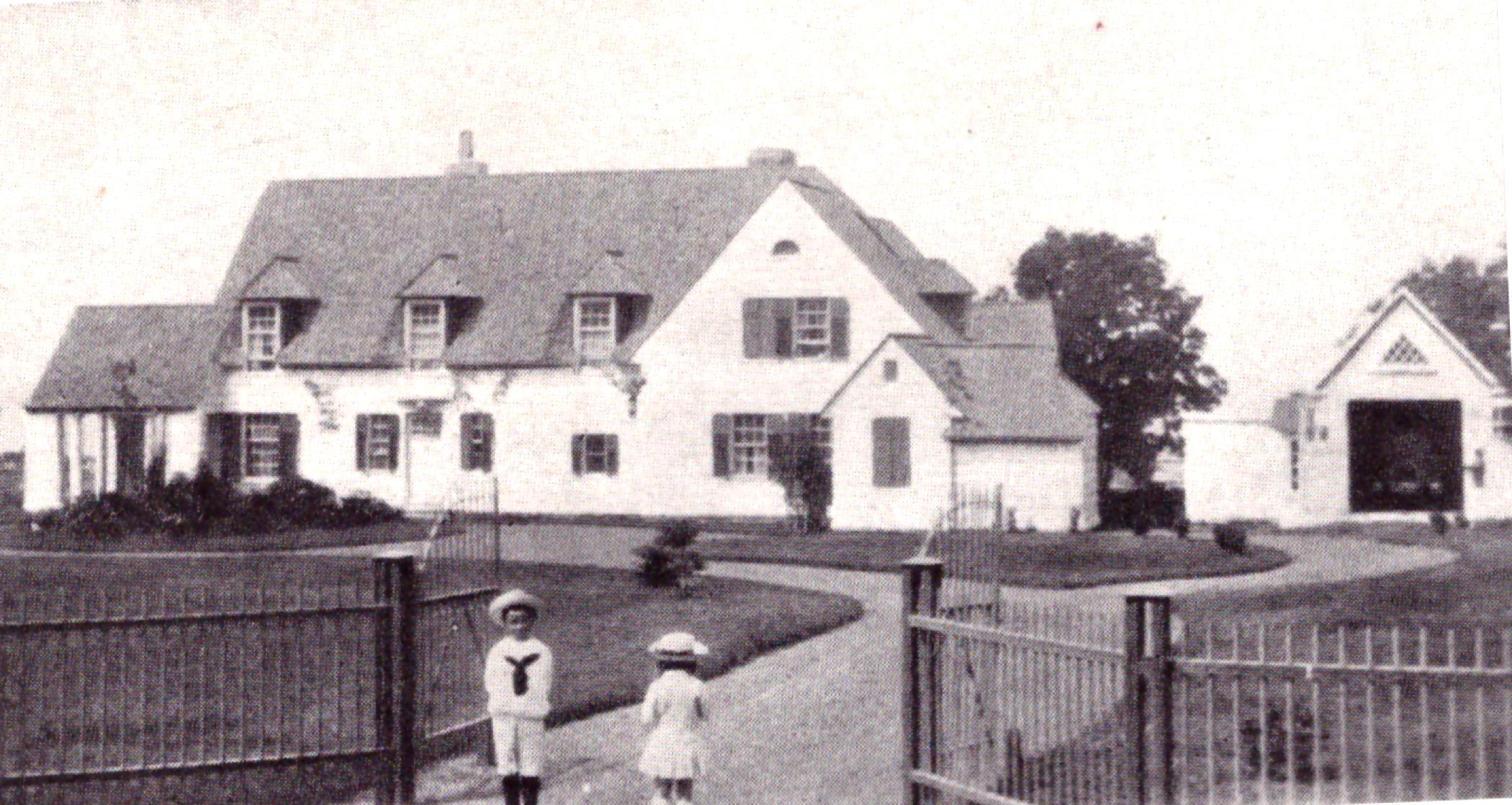 Photographie aux tons sépia d'une vaste maison (domaine de Kenneth Molson) entourée d'une clôture de fer avec portes; en avant-plan, on aperçoit deux jeunes enfants en costumes de matelots.