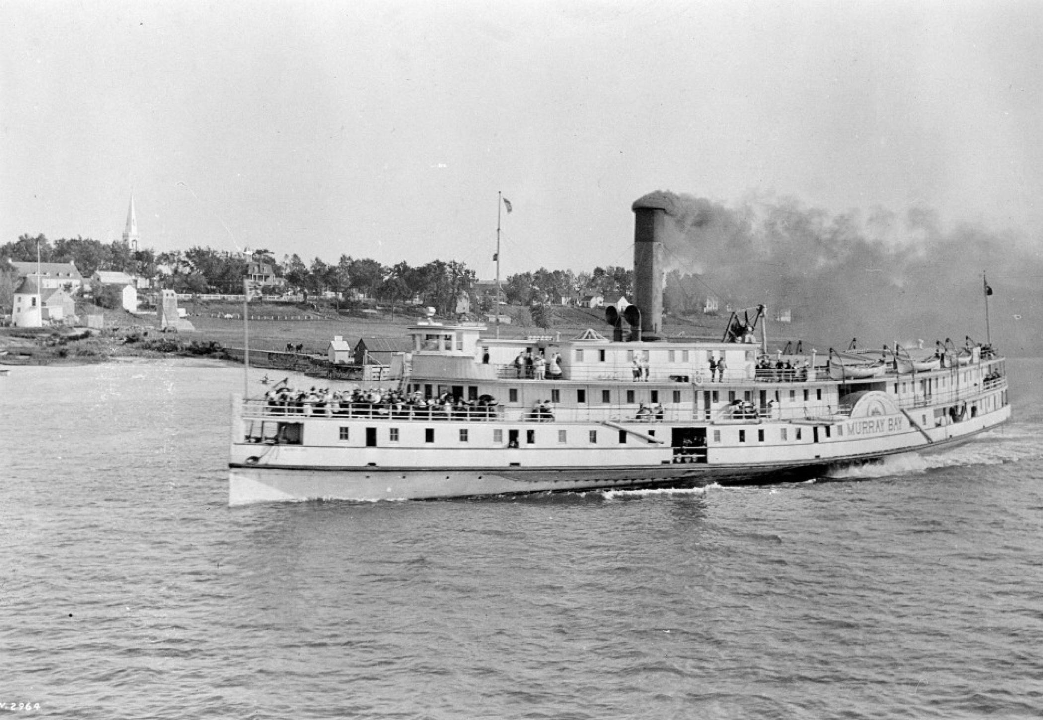 Image en noir et blanc d'un traversier à vapeur de taille moyenne en transit sur le fleuve, expulsant un nuage de fumée noire de sa cheminée, bondé de voyageurs sur son pont avant.