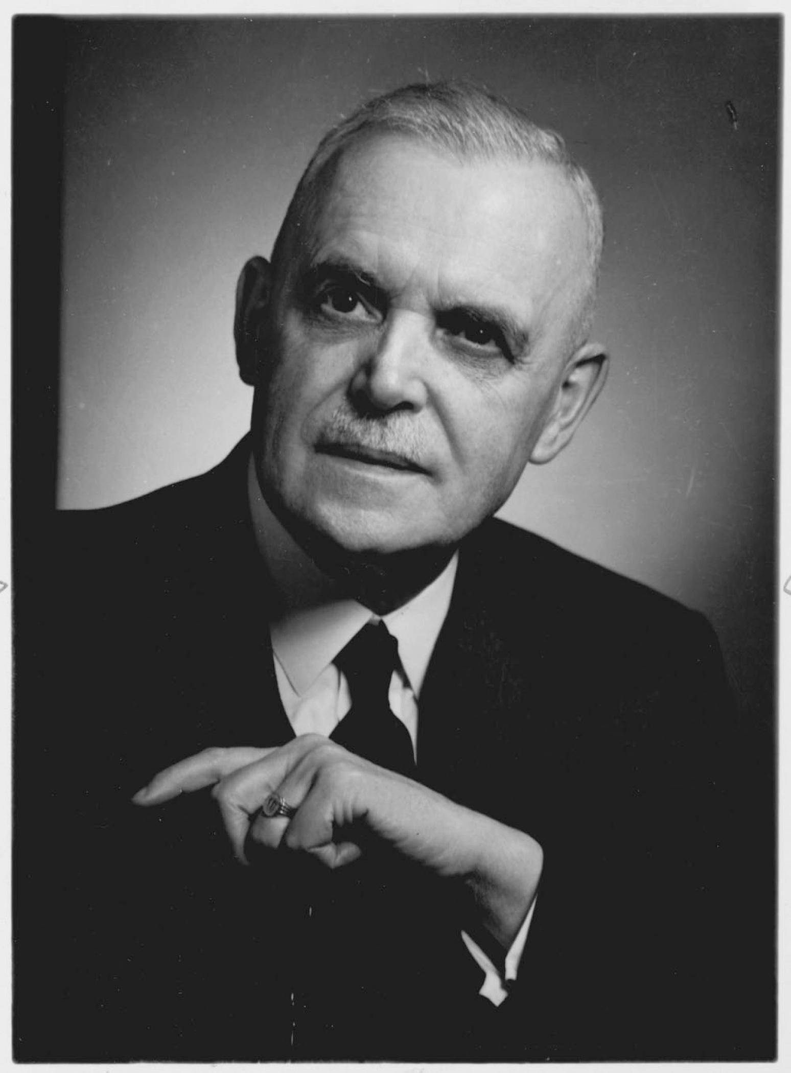 Portrait noir et blanc plan buste du l'Honorable  Louis St-Laurent en costume-cravate, son front marqué par un recul de la lisière de ses cheveux gris; ses yeux noirs lui donnant une expression autoritaire.