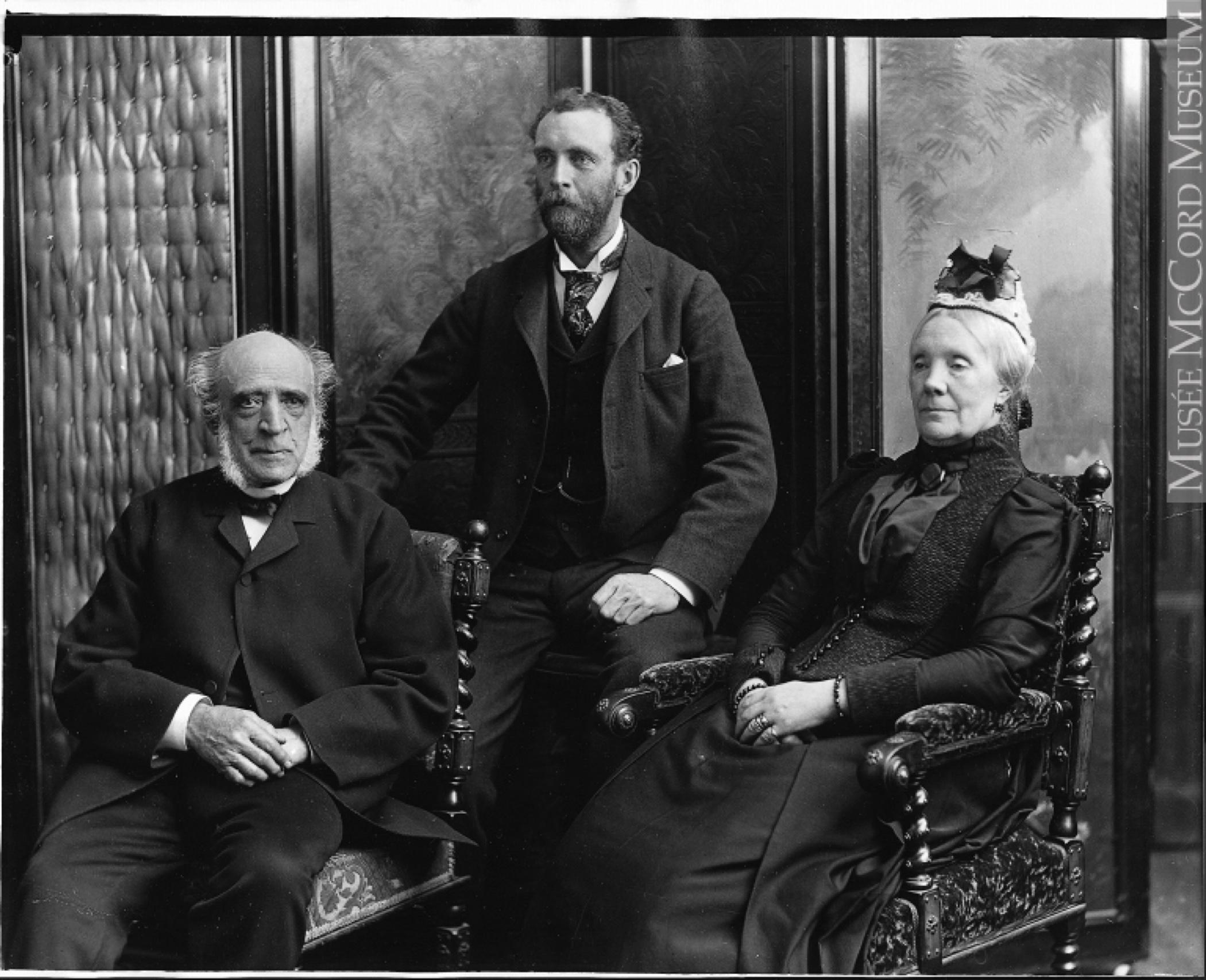 Photo officielle en noir et blanc de trois personnes (William C. Meredith, son épouse, Sofia Naters Holmes Meredith et leur fils, Henry Meredith); le couple (âgé) assis sur des chaises richement sculptées et leur fils assis derrière eux sur un tabouret.