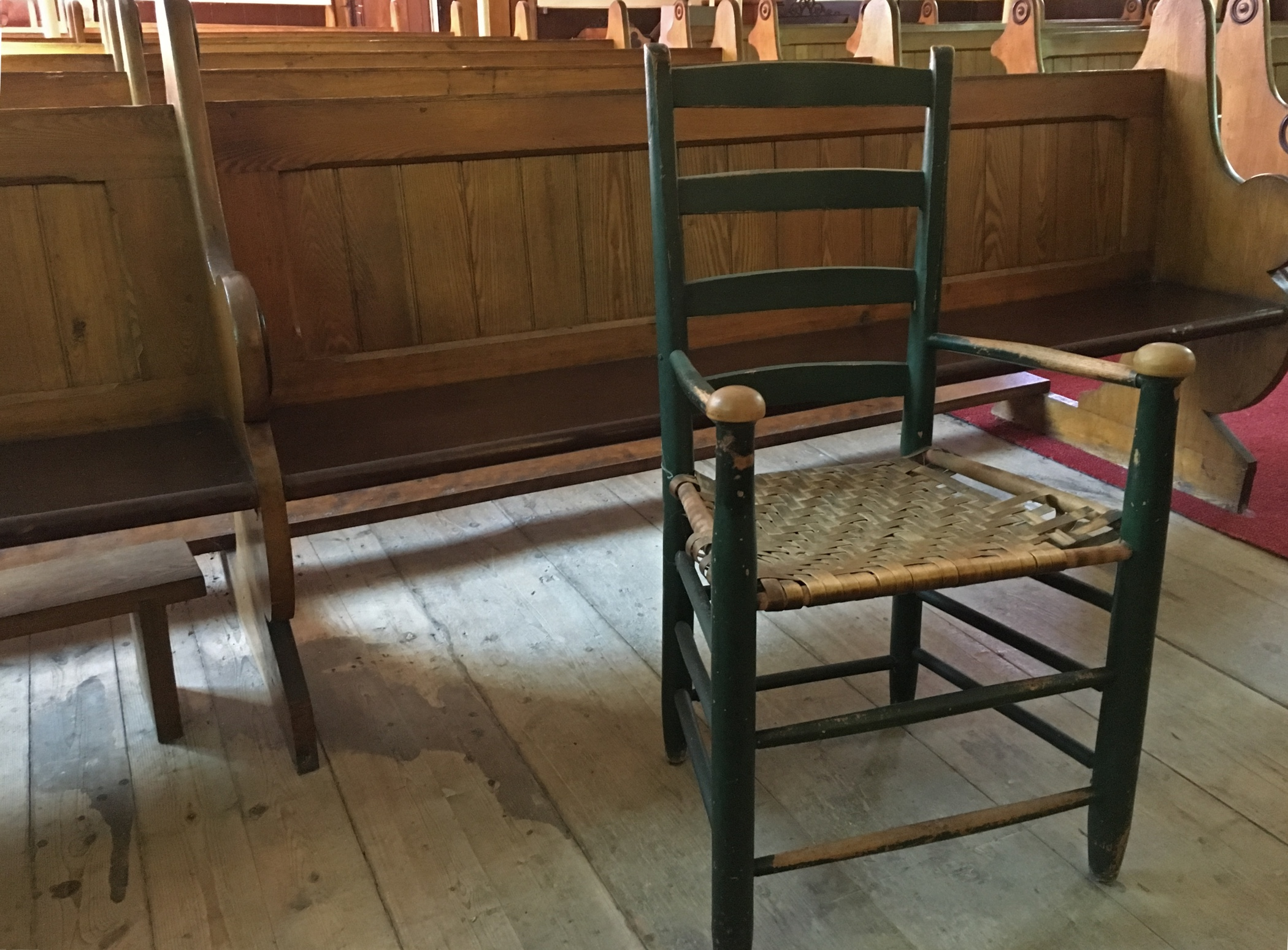 Photographie couleur d'une chaise en bois avec un siège à lattes, peinte en vert, dont on peut constater la vétusté par les lattes détachées du cadre sur un côté du siège ainsi que la peinture écaillée sur les appuie-mains des accoudoirs. La chaise se trouve devant une rangée de bancs d'église en bois. On aperçoit une surface du vieux plancher de bois franc brut.