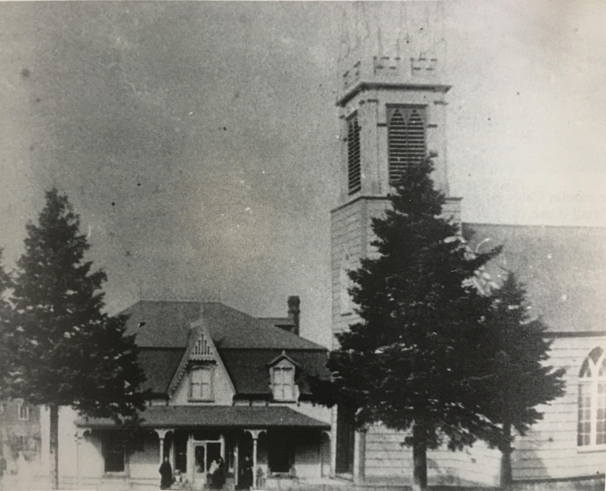 Photo noir et blanc d'une vieille église en bois, l'église anglicane St. Bartholomew surmontée d'un clocher en façade et de son presbytère à deux étages attenant.