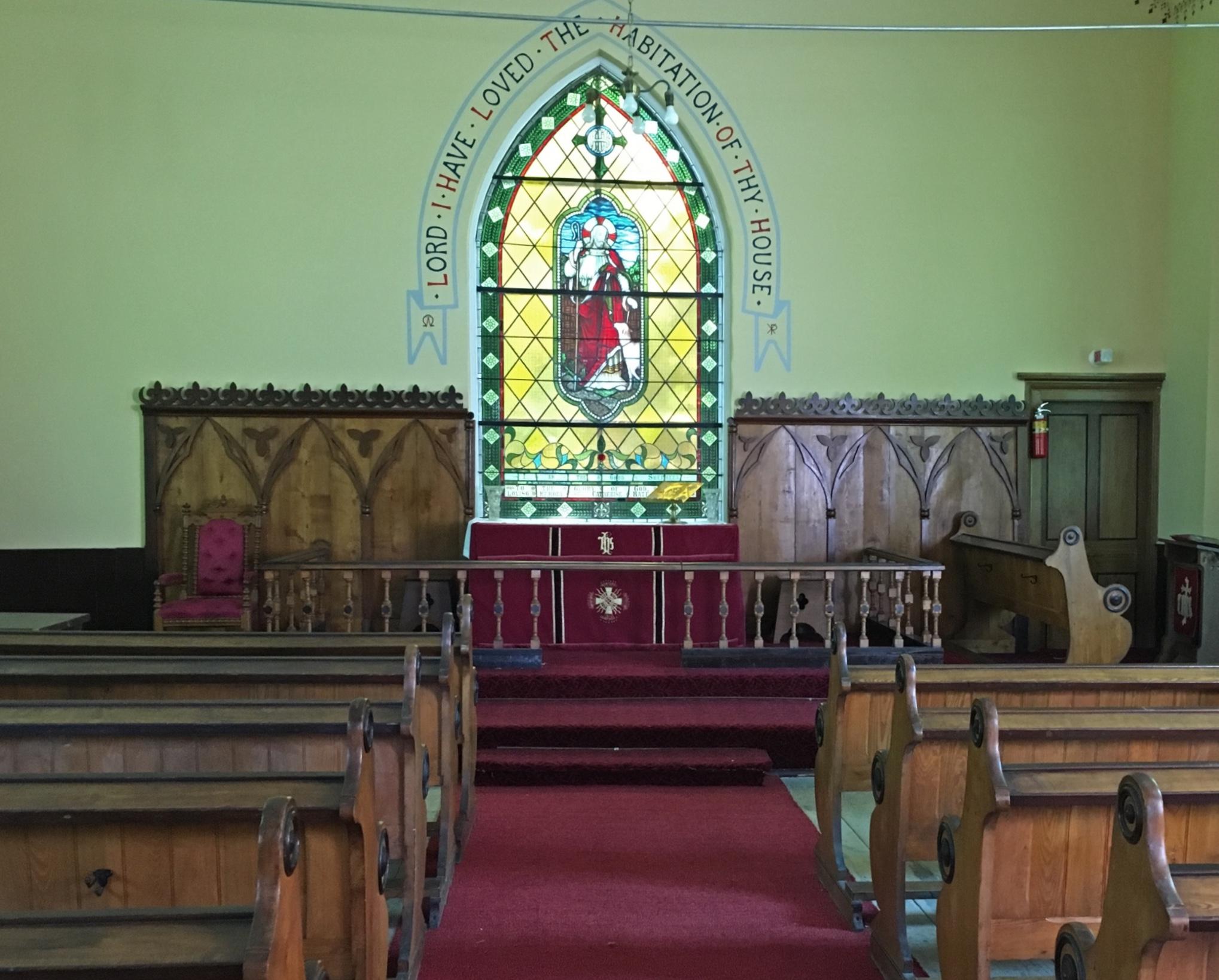 Photo couleur de l'intérieur de l'église anglicane de St. Bartholomew sur laquelle on aperçoit des rangées de bancs en bois faisant face à l'autel, lequel est orné de panneaux en bois fixés au mur sans apparat au centre duquel se trouve un vitrail.