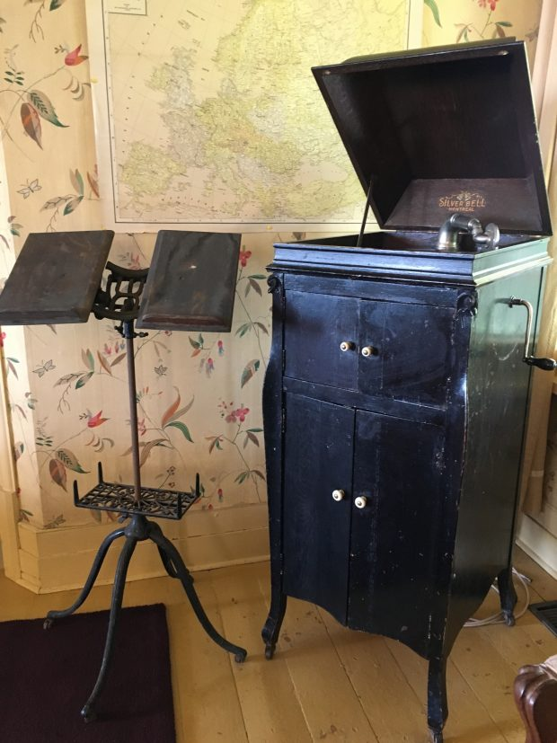 Une photo couleur d'un vieux gramophone Victrola en bois, dont le couvercle est ouvert, à côté duquel se trouve un pupitre en fonte.