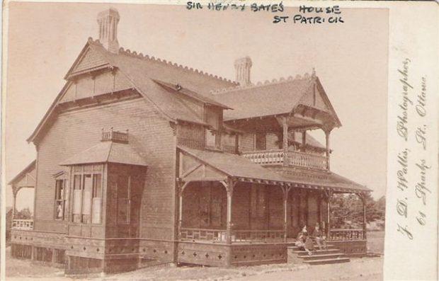 Vieille carte postale montrant une maison antique en bois à deux étages parée de boiseries et garnitures finement ciselées; deux personnes étant assises sur les marches de sa véranda.