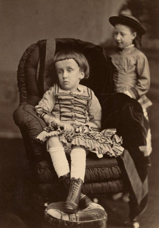 Photographie noir et blanc d'une petite fille (la jeune Mary Macdonald), assise sur une chaise, les jambes croisées devant elle, l'air absent. On dénote que sa tête est anormalement grosse, auréolée d'une chevelure noire coupée au carré avec une frange sur son large front.