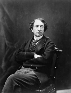 Black and white portrait of Sir John A. Macdonald, a middle-aged man with dark hair, posing in a chair in a studio, his arms folded across his chest.