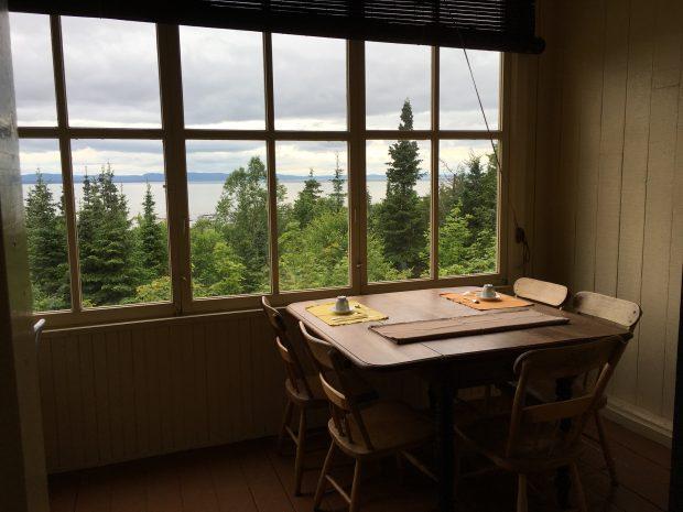 Photo couleur de l'intérieur d'une petite pièce dotée d'une fenêtre à triple vitrage à carreaux permettant une vue sur le paysage extérieur : une forêt d'arbres surplombant le fleuve sous un ciel nuageux. À l'intérieur, devant la fenêtre, est installée une petite table en bois entourée de cinq chaises en bois. La table est mise pour un petit-déjeuner pour deux personnes.