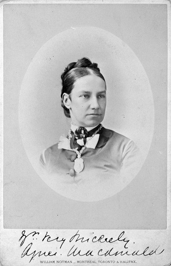 Un portrait plan buste de Lady Agnes Macdonald, alors qu'elle devait être âgée entre 30 et 35 ans, ses cheveux noirs bien serrés dans un arrangement de nattes épinglées derrière sa tête; elle est vêtue d'une chemise boutonnée, ornée d'un camée à l'encolure et d'un collier-écusson sur lequel sont gravés des détails indistincts sur la photo. Son visage affiche une expression à la fois pensive et austère.