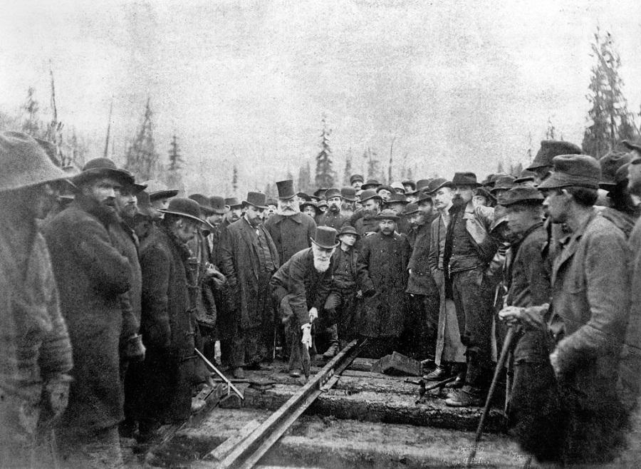 Une photo en noir et blanc datant de 1885, montrant plus d'une centaine d'hommes revêtus de manteaux de laine entourant un homme, Sir Donald A. Smith, coiffé d'un haut-de-forme, penché au-dessus d'une voie ferrée, muni d'un pic, enfonçant le dernier crampon du chemin de fer Canadien Pacifique.