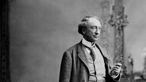 Une photo en noir et blanc de Sir John A. Macdonald, un homme âgé, vêtu d'un costume en laine, tenant dans sa main gauche une paire de lunettes.