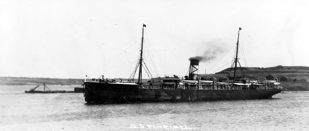 Photographie d'archive en noir et blanc. Le grand paquebot SS Florizel dans un port. Derrière le bateau à droite, on voit des maisons sur une colline, et à gauche un quai.