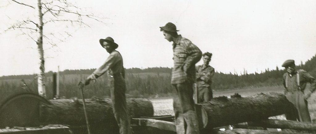 Quatre hommes travaillent à côté d'une scierie rudimentaire. La scie coupe une bûche de mélèze. Une autre bûche est sur un chariot pour être coupée après. La scierie est au milieu d'un champ.