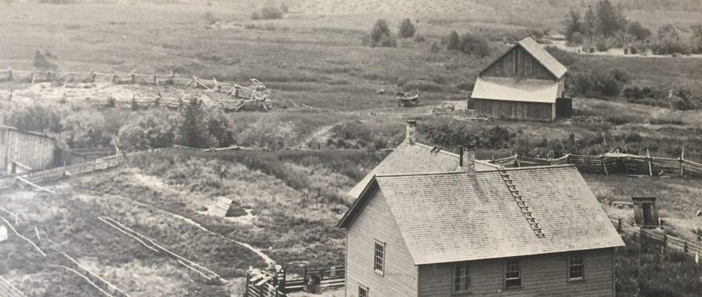 Une maison de deux étages est au centre d'une propriété pionnière. La propriété est entourée par des herbes du marécage et des arbustes. La maison est entourée par une clôture en bois. Il y a une étable et des corrals dans l'arrière-plan. Au-delà de l'étable, il y a un champ de foin.
