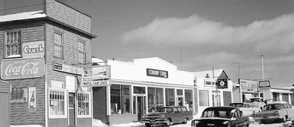 Photographie d'archives en noir et blanc. Vue de la rue. Vue de la rue Main de Windsor en direction de l'est. On voit le café Maple Leaf, le magasin Economy Store, la Banque de Montréal, le magasin Newfoundland Outfitting et le bureau de poste de Windsor. Plusieurs voitures sont dans la rue, qui est enneigée.