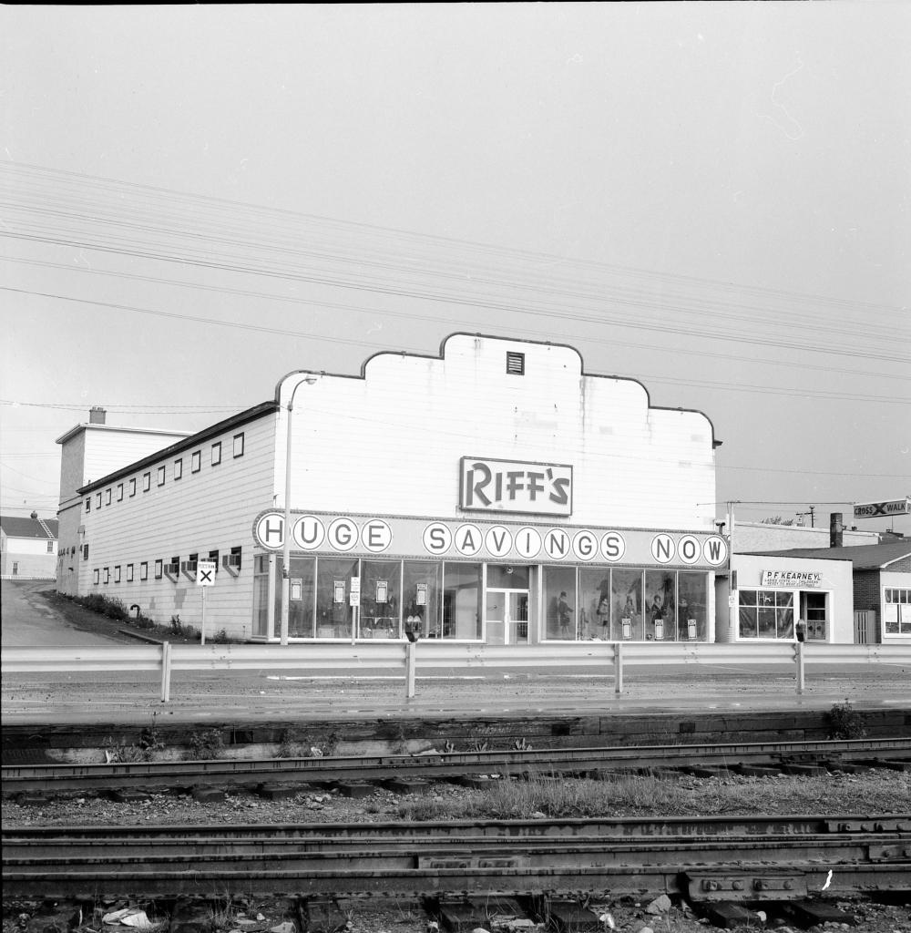 Photographie d'archives en noir et blanc. Vue de la rue. Un bâtiment est visible de l'autre côté des voies de chemin de fer. Texte du panneau accroché en travers du bâtiment : RIFF'S. En dessous : HUGE SAVINGS NOW (GROS RABAIS MAINTENANT). On aperçoit des mannequins hommes et femmes à travers les fenêtres de l'avant du bâtiment. Le magasin P.F. Kearney est à droite.