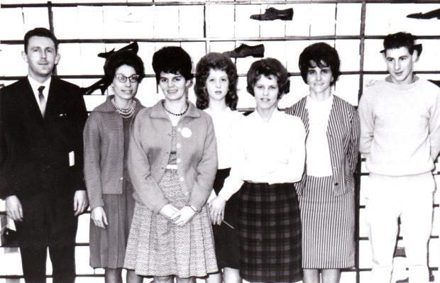 Photographie d'archives en noir et blanc. Employés devant un mur de chaussures. De gauche à droite : homme en costume-cravate, cinq femmes, et un homme portant un pantalon et une chemise à manches longues. Tous ont les cheveux foncés. Les femmes portent toutes des jupes et blouses ou des robes, et certaines portent un blazer.